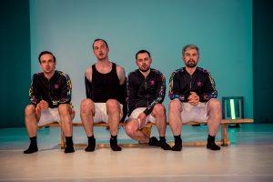 4 Männer in Sportklamotten auf einer Trainingsbank in einer Turnhalle. Aus dem Theaterstück Cezary goes to war